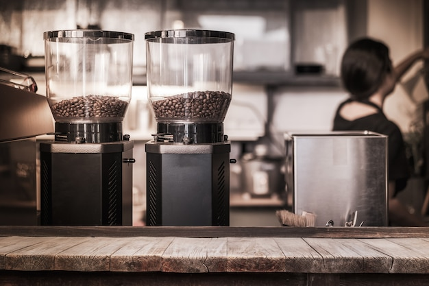 Wooden table in front of coffee bean in coffee machine in coffee shop Premium Photo