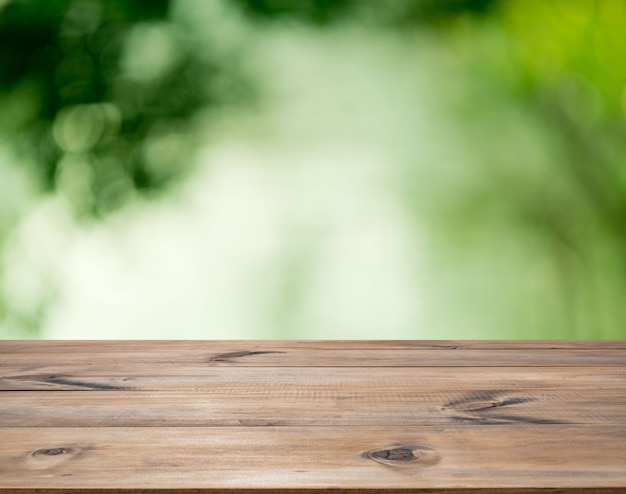 Wooden table for interior decoration design or advertising display on green bokeh background Premium Photo