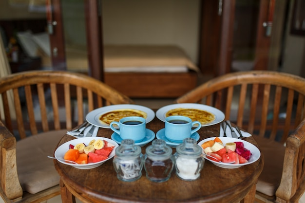 A wooden table is set on the terrace of the room. balinese tropical breakfast of fruit, coffee and scrambled eggs and banana pancake for two. on the street near the pool. Premium Photo