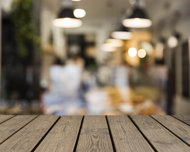 Wooden table looking out to blurred restaurant scene Free Photo