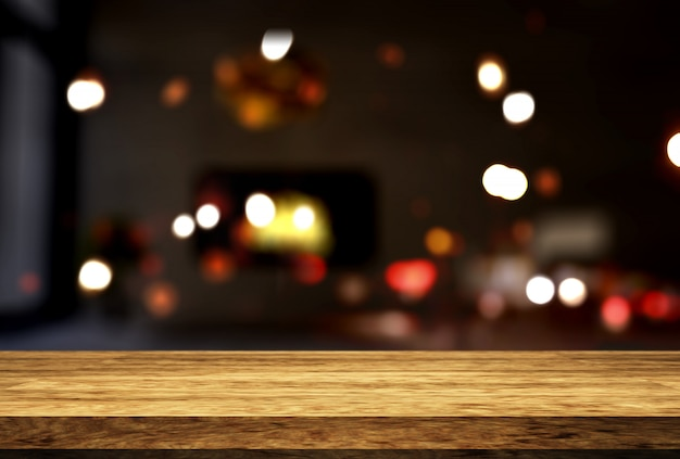 Wooden table looking out to a defocussed room interior Free Photo