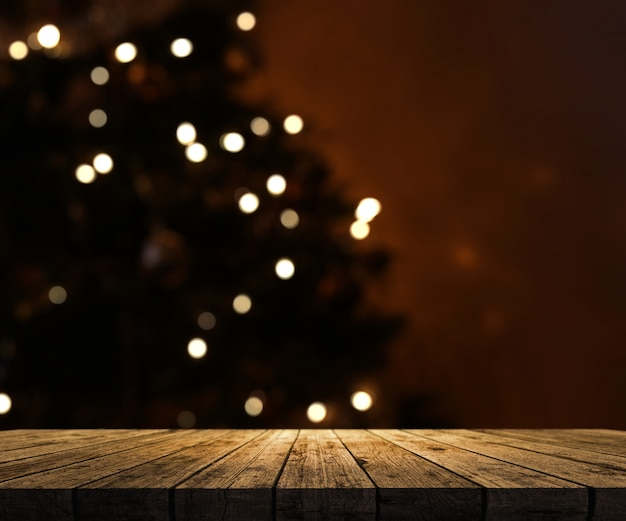 wooden table looking out to a defocussed Christmas tree Free Photo