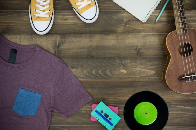 Wooden table of music composer, ukulele, notebook, audio cassettes, tape recorder and clothes Premium Photo