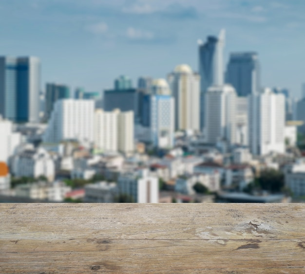 Wooden table top with blurred abstract background of bangkok downtown cityscape Premium Photo