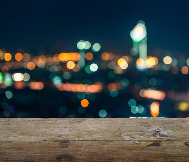 Wooden table top with blurred abstract background of bangkok night lights downtown city view with bokeh Premium Photo