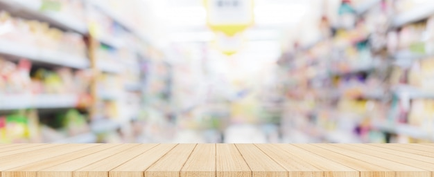 Wooden table top with blurred supermarket in background, panoramic banner. Premium Photo