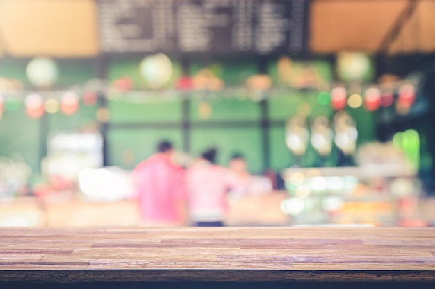 Wooden table top with view on defocused customer at restaurant Premium Photo