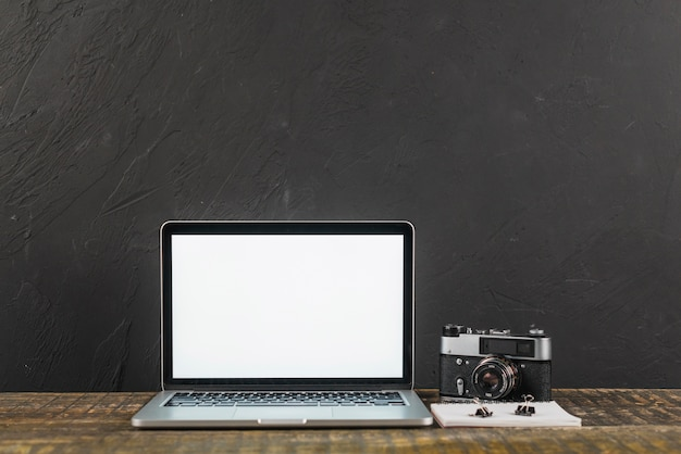 Wooden table with blank screen laptop and retro photo camera on black background Free Photo