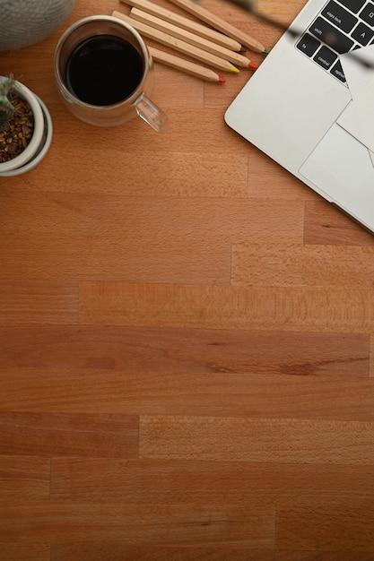 Деревянный стол с чашкой кофе и ноутбуком Premium Фотографии