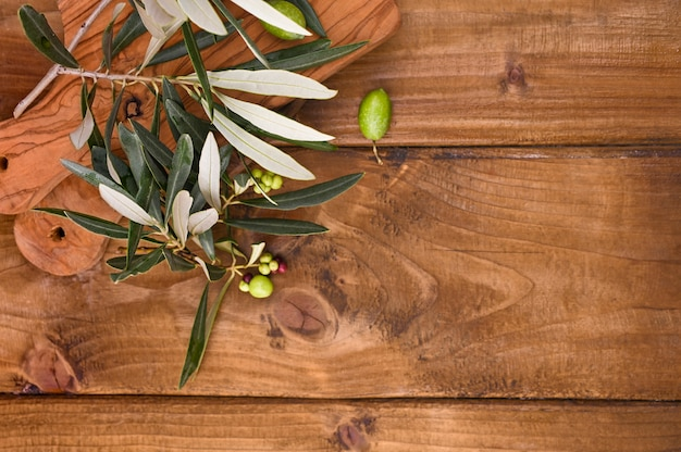 Wooden table with olives and leaves Premium Photo