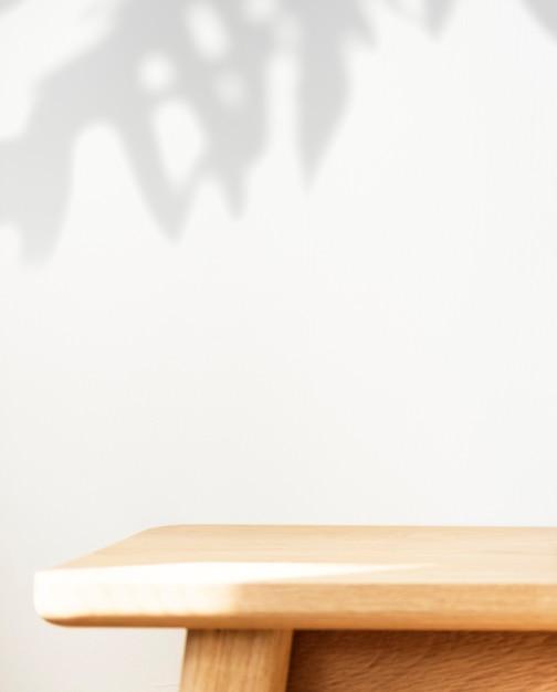 벽에 식물 그림자와 나무 테이블 무료 사진
