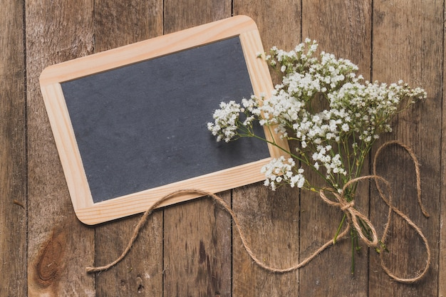 Wooden table with small blackboard and floral decoration Free Photo