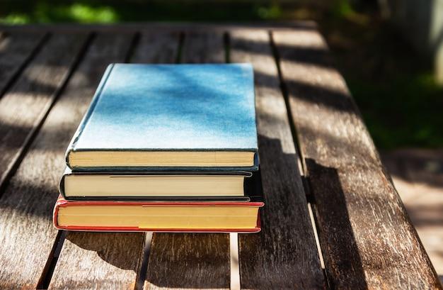 Деревянный стол с тремя книгами друг на друге днем Бесплатные Фотографии