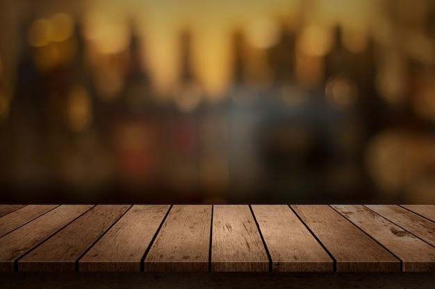 Wooden table with a view of blurred beverages bar backdrop Premium Photo
