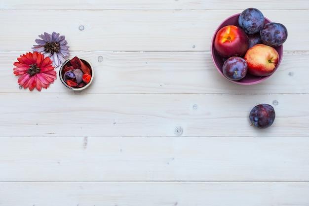 新鮮な果物と花の梅とネクタリンのテキスト付きのスペースがある木製の卓上 無料写真