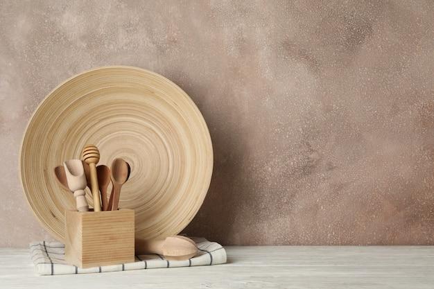 Деревянная посуда и столовые приборы на белом столе на коричневом фоне Premium Фотографии