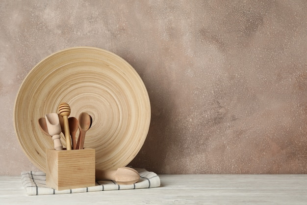 Wooden tableware and cutlery on white table against brown background Premium Photo