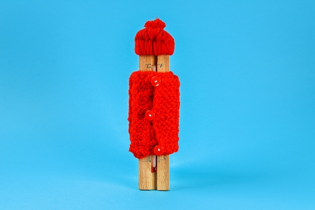 Wooden thermometer, wearing a red hat and sweater on a blue Premium Photo