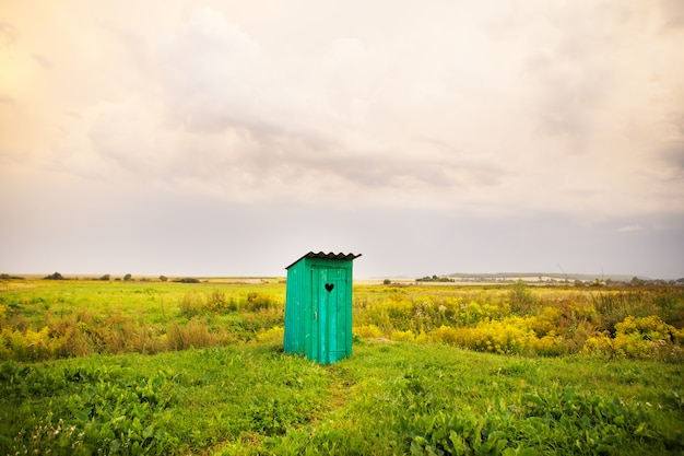 Wooden toilet with a carved window in the shape of a heart, an open field Premium Photo