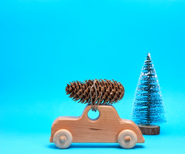 Wooden toy car carries on top a pine cone Premium Photo