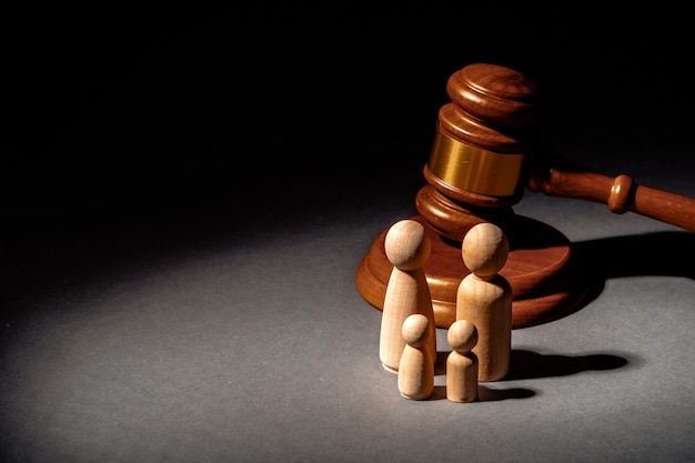 Wooden toy family and judge mallet. family divorce concept Premium Photo