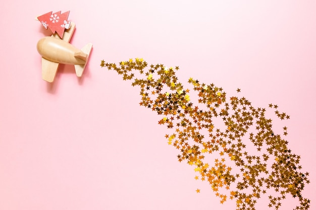Wooden toy plane with golden confetti on a pink surface Premium Photo