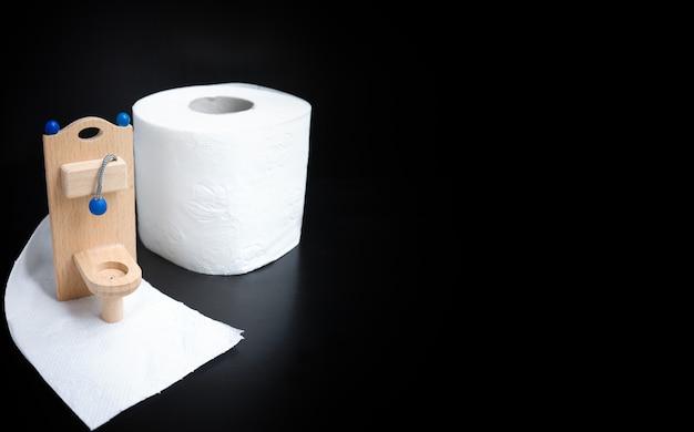 Wooden toy toilet on black Premium Photo