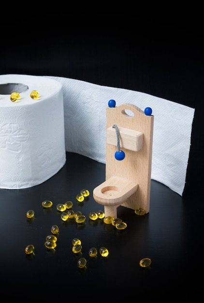 Wooden toy toilet, capsules and paper on black Premium Photo