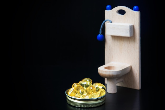 Wooden toy toilet and yellow capsules Premium Photo