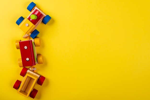 Wooden train on yellow background with space for text. Premium Photo