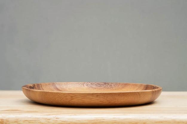 木製のテーブルと灰色の背景の木製トレイ。 Premium写真