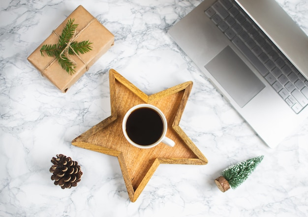 Wooden tray star cup with black coffee christmas morning gift box laptop new year concept Premium Photo