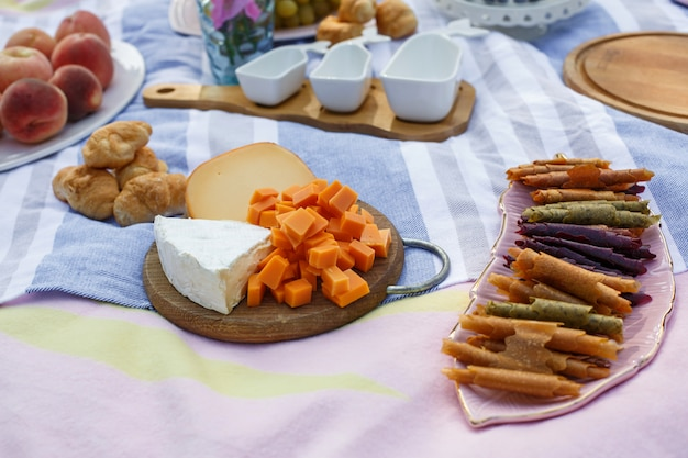 Wooden tray with cheese assorti, pastillum rolls and croissant layout on blue picnic blanket Premium Photo