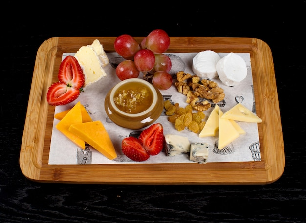 Wooden tray with cheeses, fruits and a jar of honey Free Photo