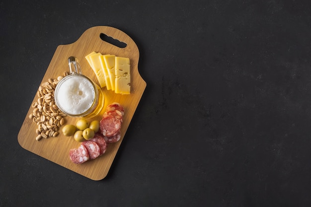 Wooden tray with delicious snack going well with beer Premium Photo