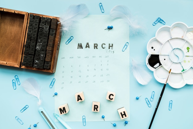 Wooden typographic blocks; feather; march blocks and march stamp on calendar with stationery against blue backdrop Free Photo