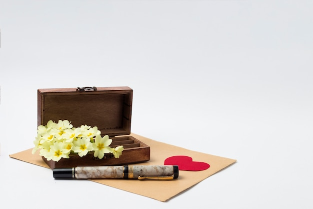 木製ヴィンテージcas、封筒、ペン、段ボールの赤いハート、白い背景に白い春の花。 Premium写真