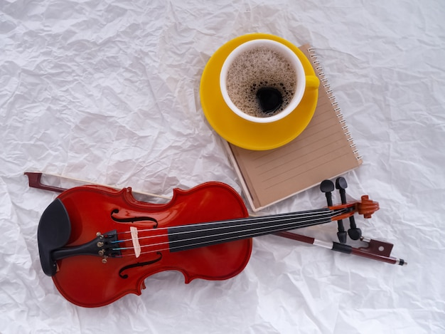 The wooden violin put beside yellow ceramic coffee cup Premium Photo