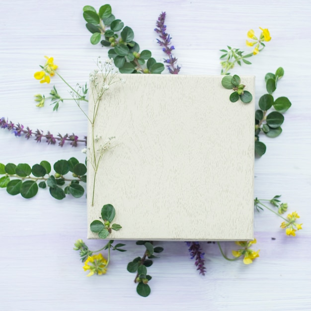 Wooden white blank frame under the flowers and leaves on textured background Free Photo
