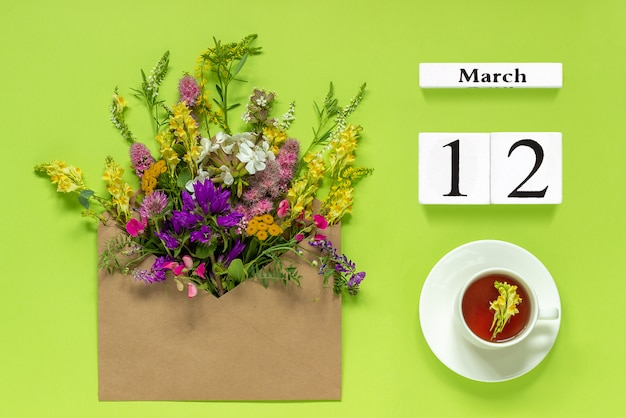 Wooden white calendar march 12. cup of tea, kraft envelope with multi colored flowers on green Premium Photo