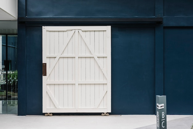 Wooden white door on a blue building wall Free Photo
