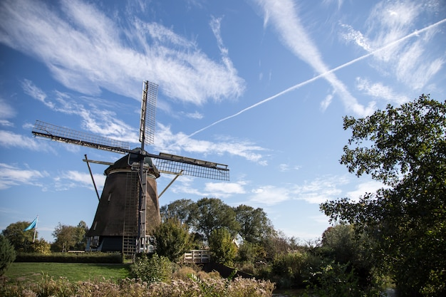 Wooden windmill on blue sky background. windmill in amsterdam Premium Photo