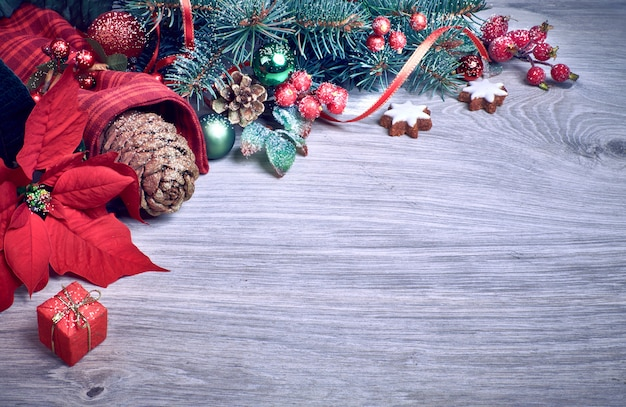 Wooden  with poinsettia and decorated christmas tree twigs Premium Photo