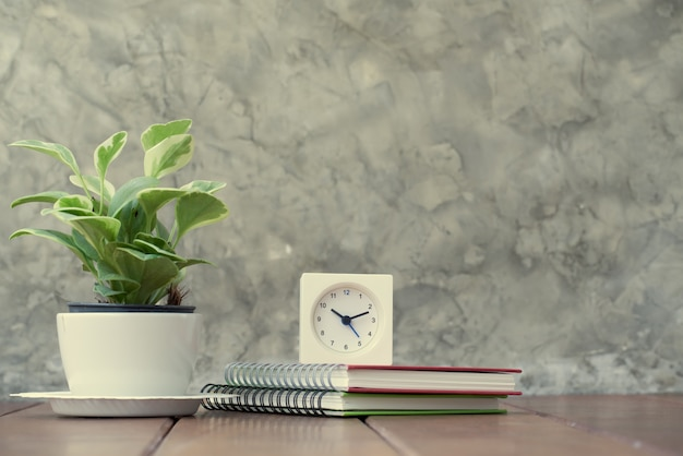 Wooden work table with notebook, alarm clock and fresh green tree in vase pot Premium Photo