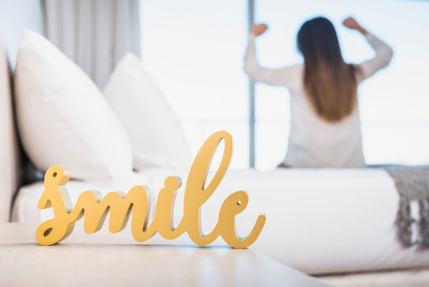 Wooden yellow smile text with her woman walking up on bed Free Photo
