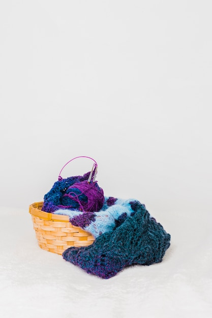 Wool scarf and ball with knitted needles in the wicker basket against white background Free Photo