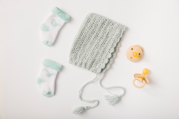 Woolen headwear; socks and pacifiers on white backdrop Free Photo