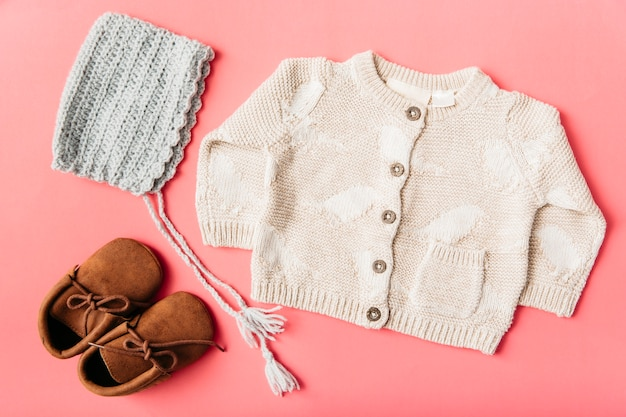 Woolen pair of shoes; cap and baby clothing on peach background Free Photo