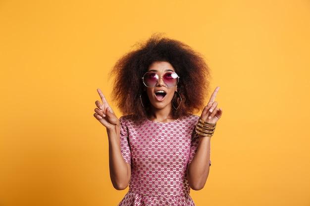 Портрет конца-вверх ретро стильного изумленного африканского wooman в солнечных очках указывая с 2 пальцами вверх, смотря вверх Бесплатные Фотографии