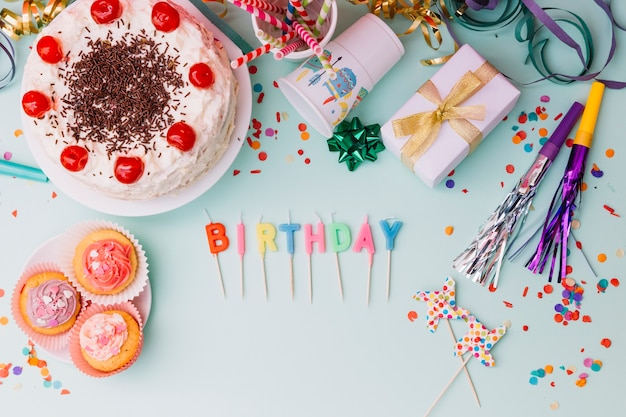 Word birthday candles with party accessories and cake on blue backdrop Free Photo